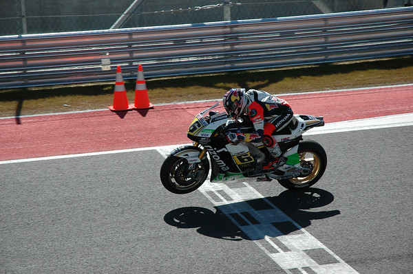 Bradl lifts a wheel over the start/finish line.